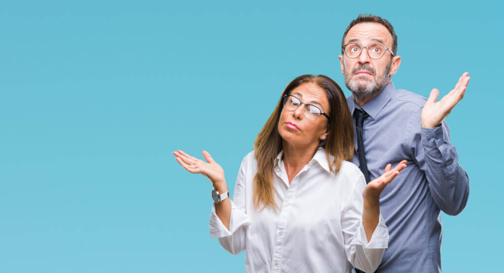 Middle age hispanic couple in love wearing glasses over isolated background clueless and confused expression with arms and hands raised. Doubt concept.